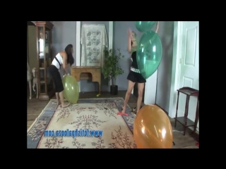 2 girls sit to pop big balloons